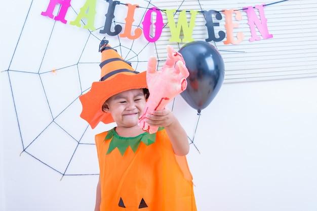 Lustiges glückliches kind im halloween-kostüm mit kürbis jack mit spinnennetz