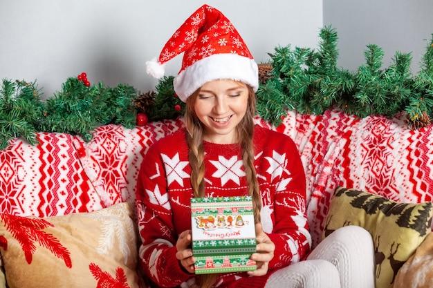 Lustiges glückliches mädchen in santa claus hat öffnet weihnachtsgeschenkbox mit geschenk nach innen