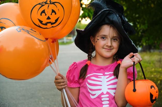 Lustiges halloween-kindermädchen mit make-up auf dem gesicht in karnevalskostümen im freien.