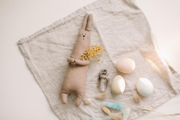 Lustiges handgemachtes häschenspielzeug des glücklichen osterkonzepts und hühnereier