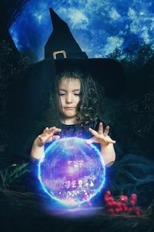 Lustiges hexenmädchen zaubert mit einem magischen ball.