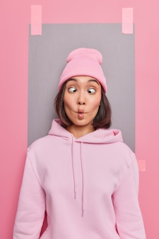 Lustiges hipster-mädchen macht fischlippen kreuzt die augen grimassen bei der kamera trägt rosa hut und sweatshirt posiert im innenbereich verputzte werbetafeln, um ihre werbung zu platzieren, die vorgibt, dumm zu sein