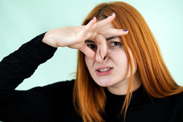 Lustiges hübsches rothaariges mädchen, das schlechtes geruchszeichen mit ihren fingern zeigt.