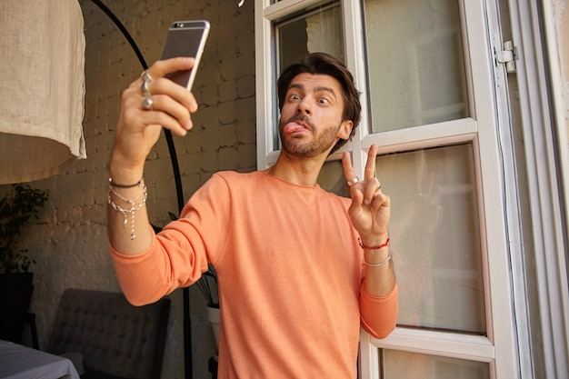 Lustiges innenporträt des hübschen bärtigen mannes, der telefon in der hand hält und sich auf fenster stützt, lächerliche gesichter macht und friedensgeste zeigt, selfie mit handy nehmend