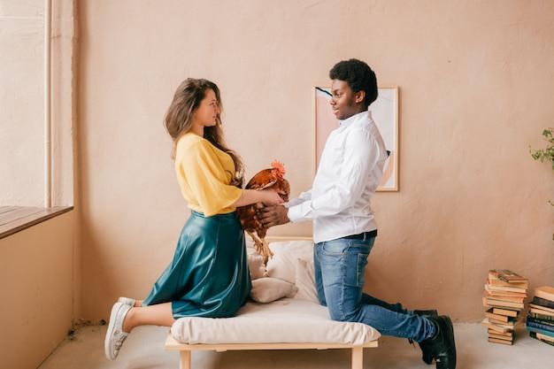 Lustiges interraciales paar, das huhn in den händen im hauptinnenraum hält.