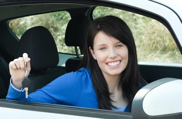 Lustiges jugendlich mädchen, das in ihrem auto hält schlüssel sitzt