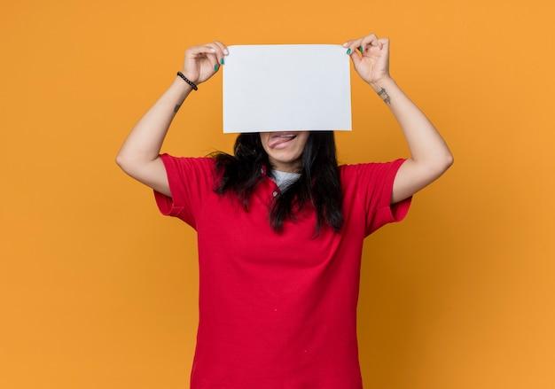 Lustiges junges brünettes kaukasisches mädchen, das rotes hemd trägt, ragt heraus zunge heraus, die papierblatt vor gesicht lokalisiert auf orange wand hält
