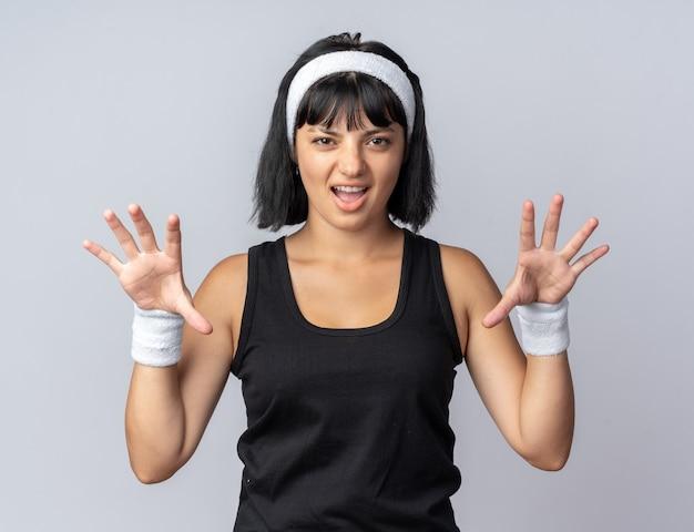 Lustiges junges fitness-mädchen mit stirnband, das erschreckend in die kamera schaut und krallen wie eine katze gestikuliert