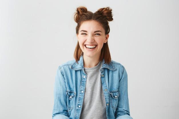 Lustiges junges glückliches fröhliches mädchen mit zwei brötchen, die lächelnd lachen.
