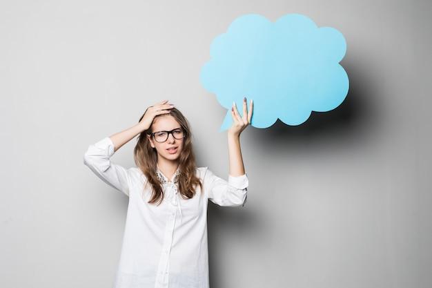 Lustiges junges hübsches studentenmädchen hält blaue chatwolken über ihrem kopf lokalisiert auf weißem hintergrund