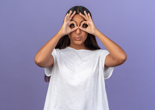Lustiges junges mädchen im weißen t-shirt, das durch die finger in die kamera schaut und eine binokulare geste auf blauem hintergrund macht