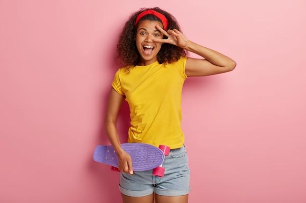 Lustiges junges mädchen mit dem lockigen haar, das im gelben t-shirt aufwirft