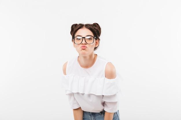 Lustiges junges mädchen mit doppelter brötchenfrisur, die brillen verziehend und blasende lippen trägt, lokalisiert auf weiß