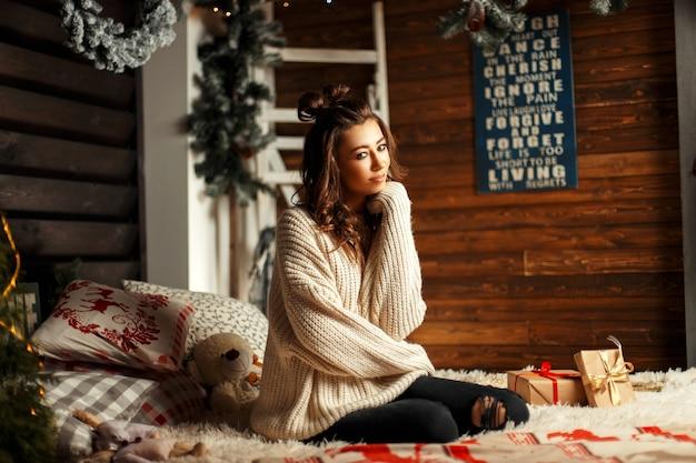 Lustiges junges mädchen mit einem haarschnitt in einem weinlesepullover mit geschenken auf dem bett mit weihnachtsdekorationen