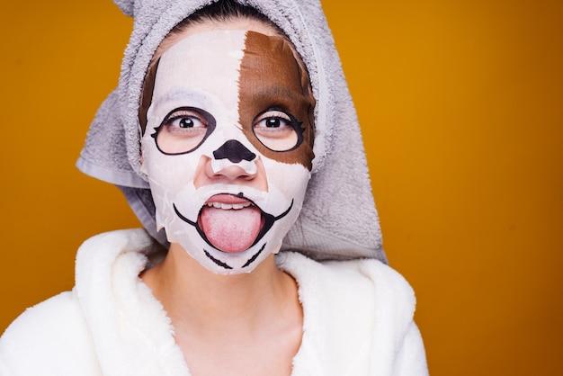 Lustiges junges mädchen mit einem handtuch auf dem kopf, das zunge zeigt, auf gesichtsmaske mit einem bild der schnauze eines hundes
