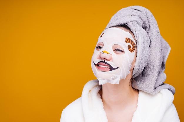 Lustiges junges mädchen mit einem handtuch auf dem kopf lächelnd, auf gesichtsmaske mit hundegesicht