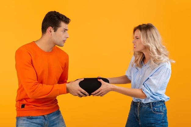 Lustiges junges paar, das für drahtlosen lautsprecher kämpft, der musik bunten stil auf orange hört