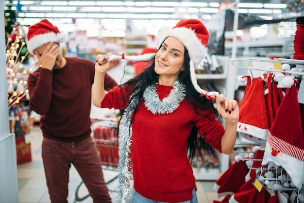 Lustiges junges paar, das weihnachtskleidung im supermarkt, familientradition anprobiert. dezember einkauf von urlaubsartikeln und dekorationen
