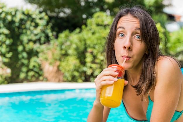Lustiges junges weibliches trinkendes getränk im urlaub