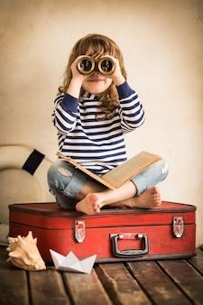 Lustiges kind, das drinnen mit spielzeugsegelboot spielt. reise- und abenteuerkonzept