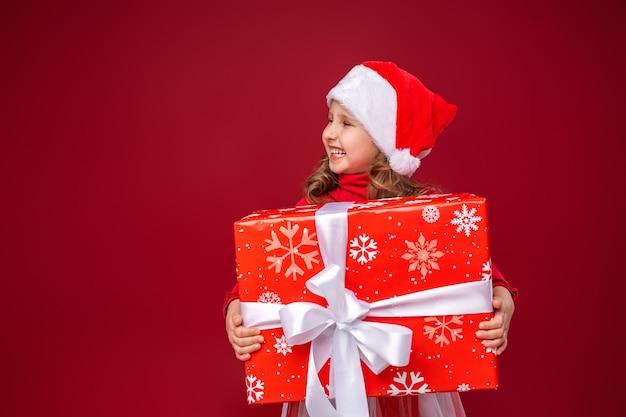 Lustiges kind, das ein geschenk in seinen händen hält, schaut weg, um geschenke zu geben.