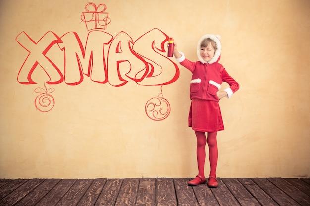 Lustiges kind, das ein graffiti macht. weihnachtsferienkonzept