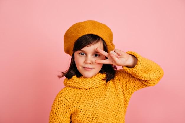 Lustiges kind, das mit friedenszeichen aufwirft. kaukasisches jugendliches mädchen im gelben outfit.