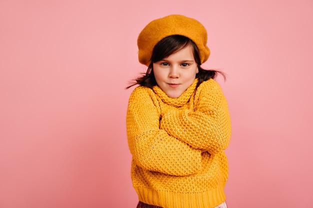 Lustiges kind, das mit verschränkten armen aufwirft. das jugendliche mädchen trägt gelbe kleidung.