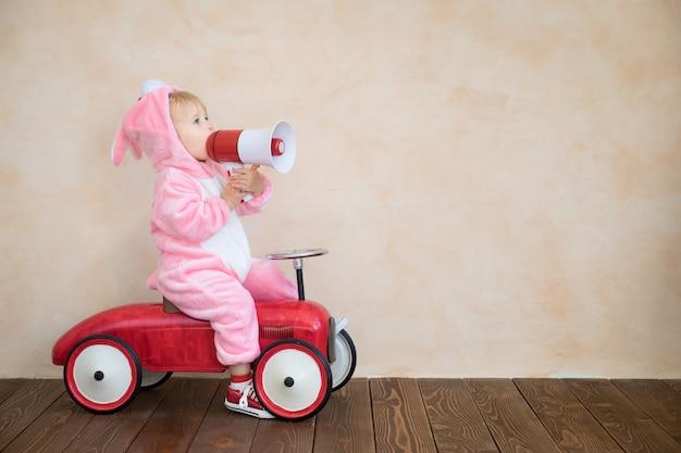 Lustiges kind, das osterhasen trägt. kinder, das spielzeugauto zu hause reitet.