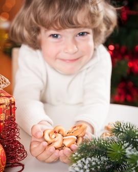 Lustiges kind, das plätzchen gegen weihnachtsbeleuchtung hält. konzentrieren sie sich auf cookies