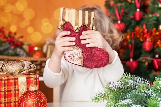 Lustiges kind, das rote socke gegen weihnachtsdekorationshintergrund hält
