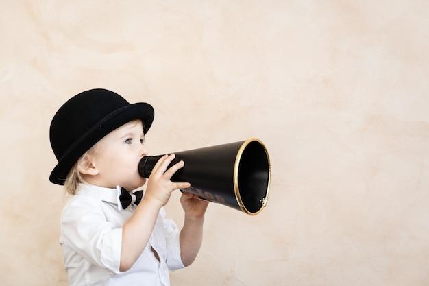Lustiges kind, das zu hause spielt. kind, das durch vintage-megaphon schreit. kommunikations- und retro-kinokonzept