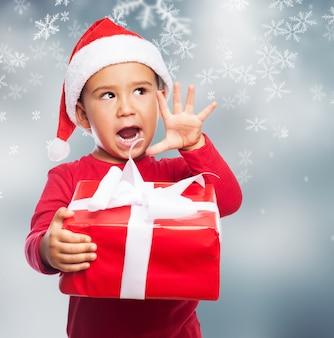 Lustiges kind ein weihnachtsgeschenk mit seiner rechten hand hält