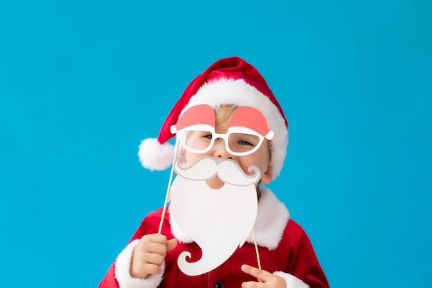 Lustiges kind gekleidetes weihnachtsmann-kostüm gegen blauen hintergrund. glückliches kind, das spaß zu hause hat. weihnachtsferienkonzept