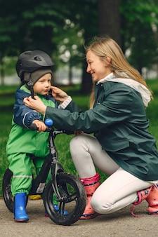 Lustiges kind in den regenstiefeln, die in einem regenpark spielen