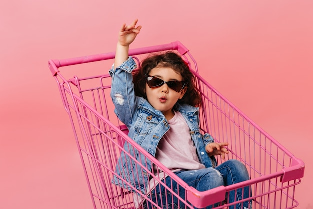 Lustiges kind in der sonnenbrille, die im einkaufswagen sitzt. studioaufnahme des glücklichen kleinen mädchens in der jeansjacke.