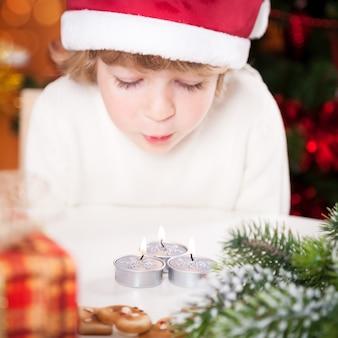 Lustiges kind in weihnachtsmütze bläst brennende weihnachtskerzen aus fokus auf kerzen