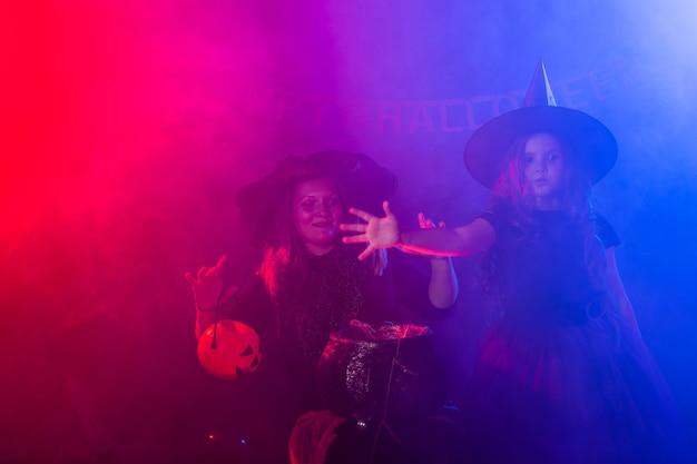 Lustiges kind mädchen und frau in hexenkostümen für halloween mit kürbis jack und hund
