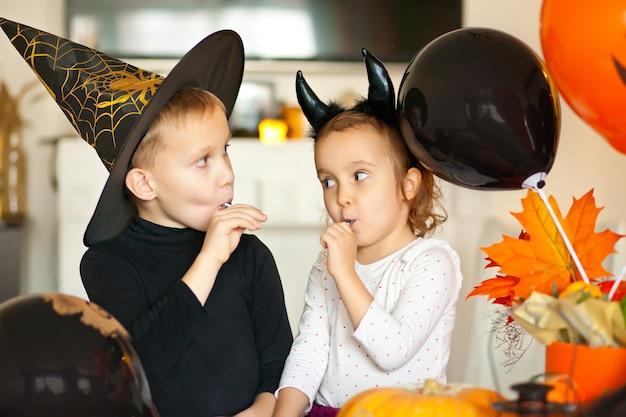 Lustiges kind mädchen und jugendlich junge in hexe und bösen kostümen für halloween-party, die süßigkeiten lolly pops essen und spaß haben