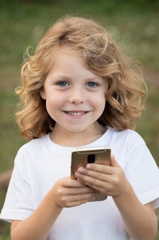 Lustiges kind mit dem langen haar, das ein mobile hält