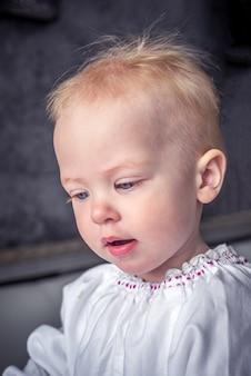 Lustiges kind mit einem blonden haar und blauen augen