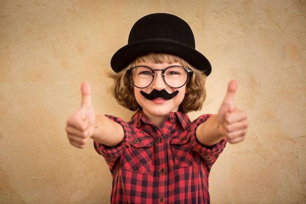 Lustiges kind mit falschem schnurrbart. glückliches kind, das zu hause spielt