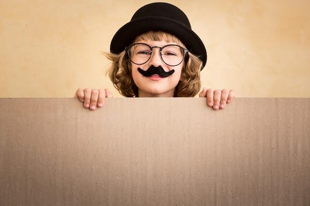 Lustiges kind mit gefälschtem schnurrbart, das banner leer hält