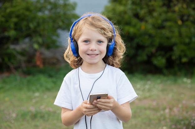 Lustiges kind mit hörender musik des langen haares mit blauen hadphones und einem mobile