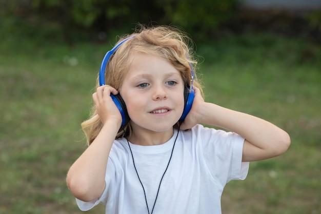 Lustiges kind mit hörender musik des langen haares mit blauen hadphones