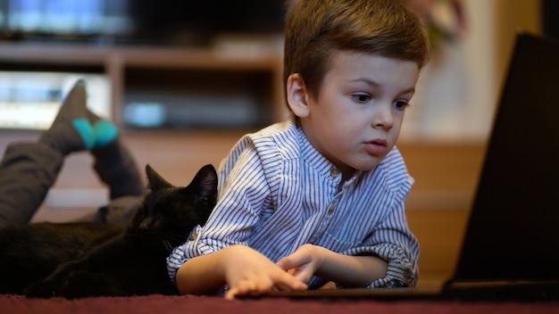 Lustiges kind mit kätzchen, das einen laptop zu hause benutzt