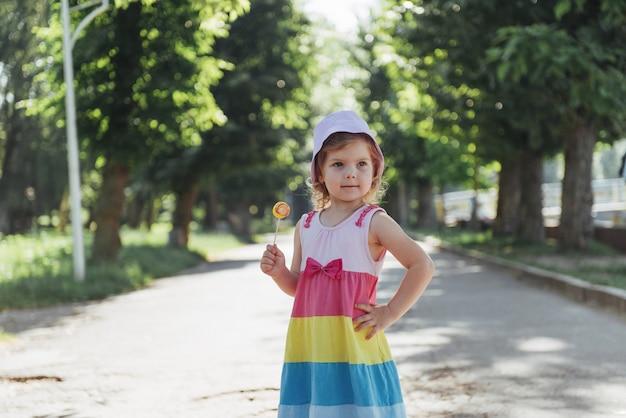 Lustiges kind mit süßigkeitenlutscher, glückliches kleines mädchen, das groß isst