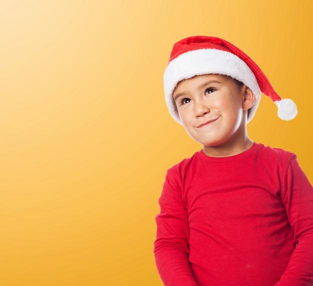 Lustiges kind mit weihnachtsmütze mit orangefarbenen hintergrund