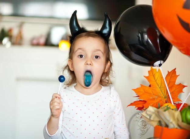 Lustiges kindermädchen im bösen kostüm für halloween, das süßigkeiten lolly pop isst und spaß hat.