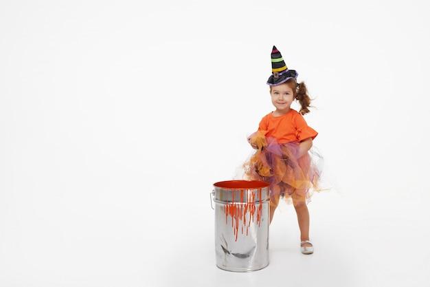 Lustiges kindermädchen im hexenkostüm für halloween auf weiß